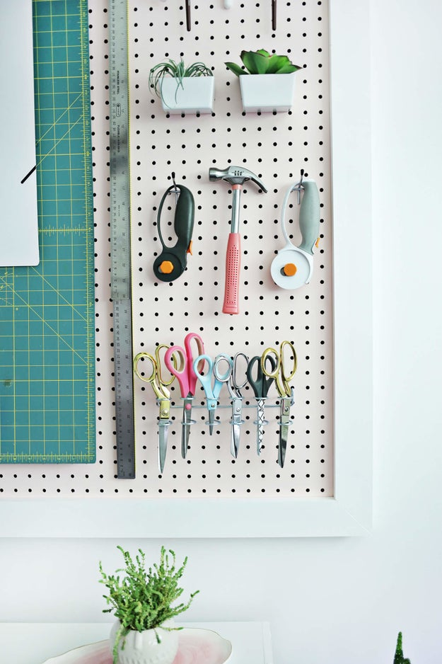 Rig up a handy pegboard by framing it and hanging hooks fit for your favorite crafting tools. Throw in some plants there, too!