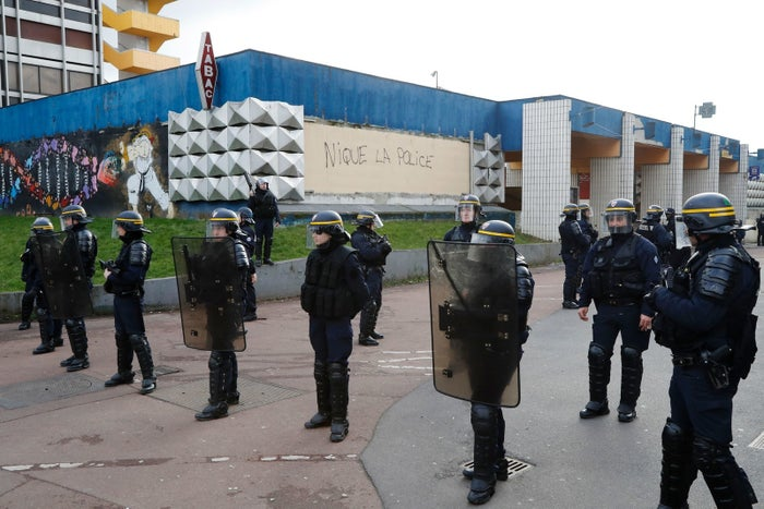 """Riot officers outside the local police station in Aulnay-sous-Bois on Monday. The graffiti on the wall reads, """"Fuck the police."""""""