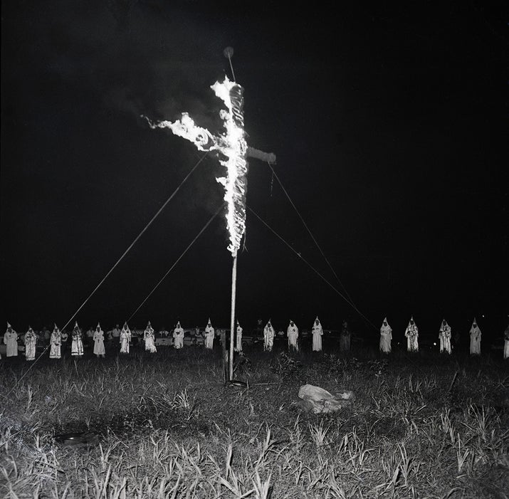 Klansmen form a circle around a burning cross at a rally in Albany, Georgia, which an estimated 3,000 persons attended in 1962.