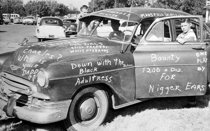Roy Lee Howlett, 14, stands beside a car painted with signs protesting the desegregation of Mansfield High School in Dallas on Aug. 31, 1956.