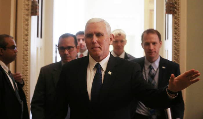 Vice President Mike Pence waves while leaving a Senate policy luncheon.