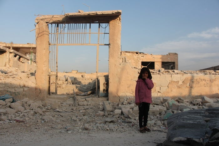 Baraa, 7, standing in front of her damaged school.