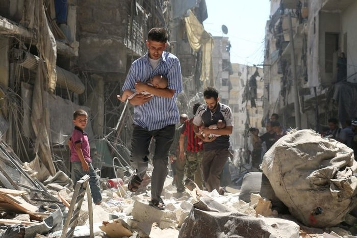 Babies are carried away from destroyed buildings following an air strike in Aleppo, Syria, in 2016.