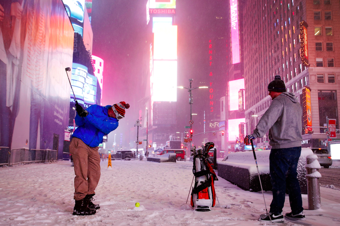 Two men play golf with a tennis ball in Times Square.