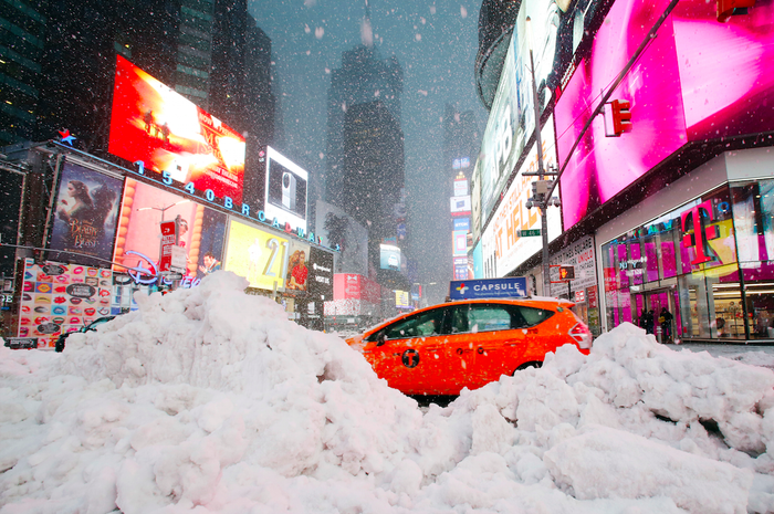 A taxi drives past piles of snow in Times Square.