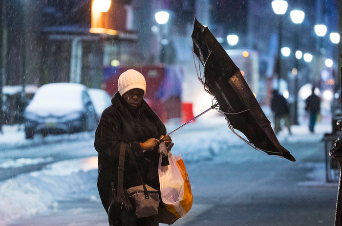 A woman's umbrella is flipped inside out by the wind in Philadelphia as a snowstorm pounded the US northeast on Tuesday.