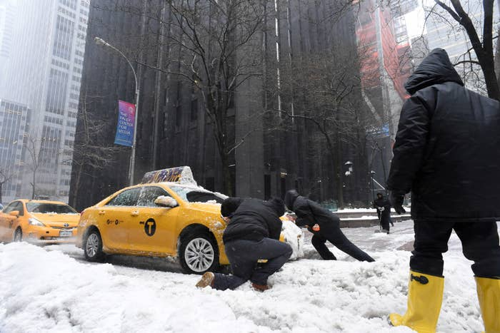 Men try to push a cab stuck in the snow on a street in New York.