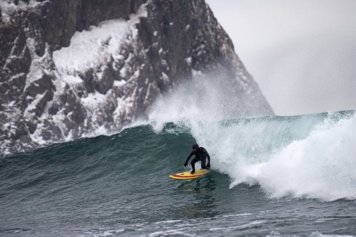 A surfer rides a wave above the Arctic Circle earlier this month.