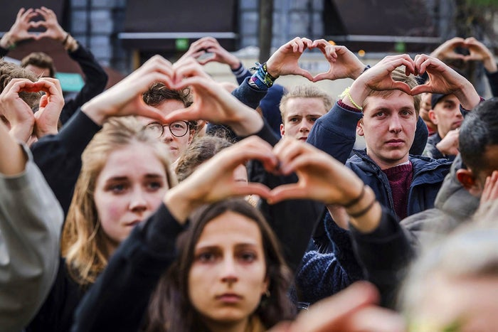 People make the shape of a heart with their hands as they observe a moment of silence at the Bourse in Brussels during the one-year anniversary of the Brussels attack.
