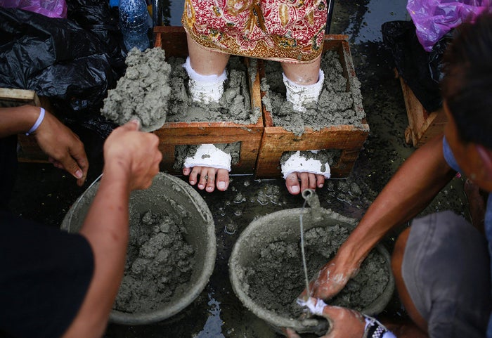 An activist has her feet cemented in a wooden case during a rally outside the presidential palace in Jakarta, Indonesia, protesting the operation of a cement factory in Kendeng, Central Java. Dozens of farmers and activists opposed to the factory also had their feet encased in concrete during the days-long protest in Jakarta.