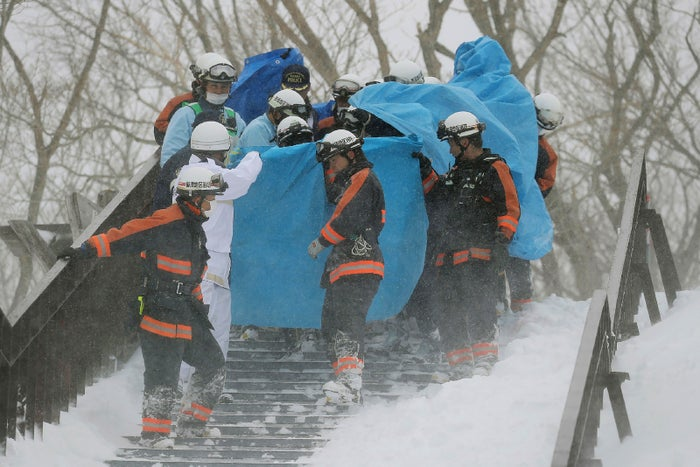 Firefighters carry a survivor they rescued from the site.