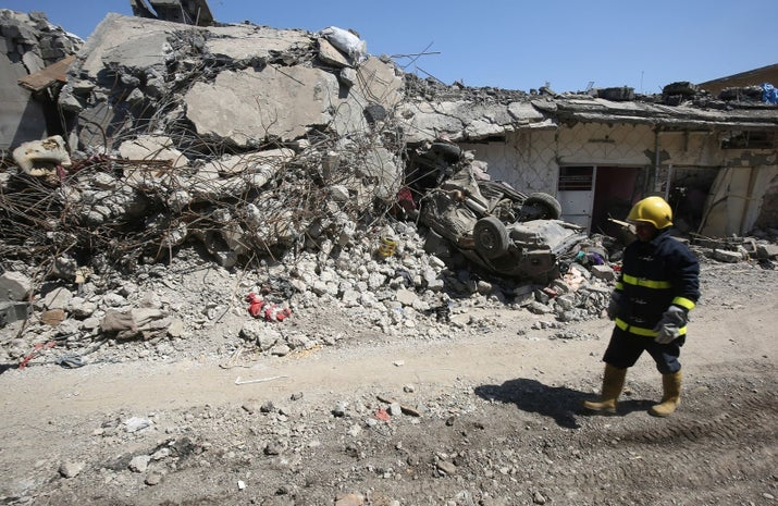 An Iraqi firefighter inspects the damage in the Mosul al-Jadida area