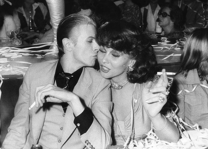 David Bowie and Dutch actor and singer Romy Haag have a smoke at the Alcazar nightclub in Paris during 1976.