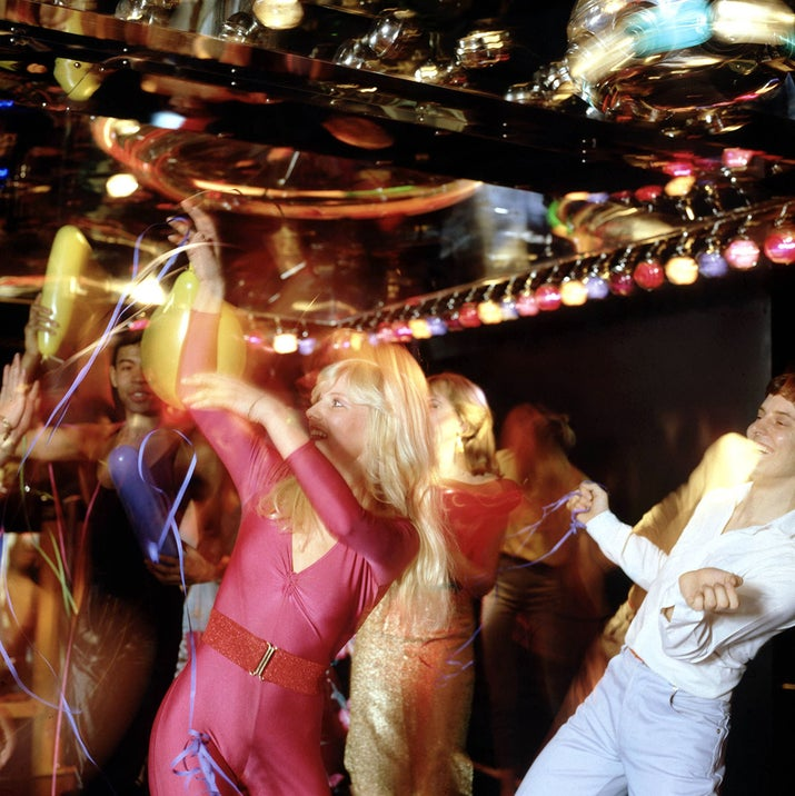 A group of partygoers join in a synchronized dance number in an unidentified club, circa 1977.