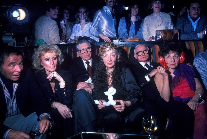 A group of older men and women relax on the sidelines of a disco club in New York City in 1978.