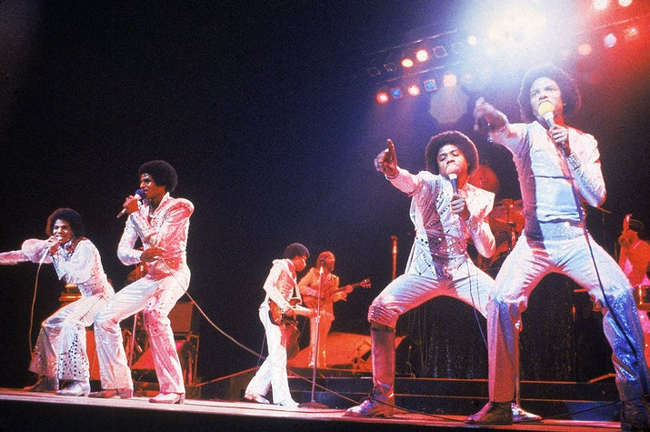 The Jacksons perform during a concert, circa 1975.