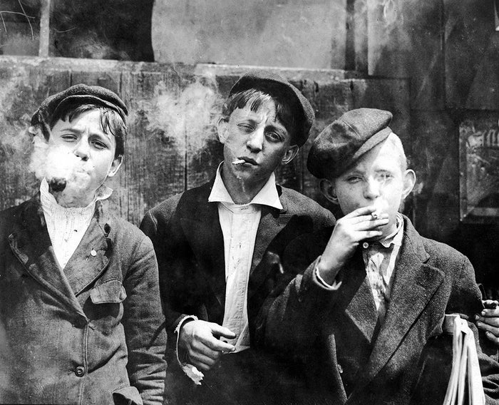 A group of newsboys have a smoke during their break in St. Louis, May 1910.