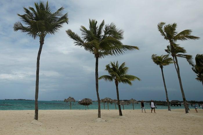 People walk along a beach in the Bahamas.