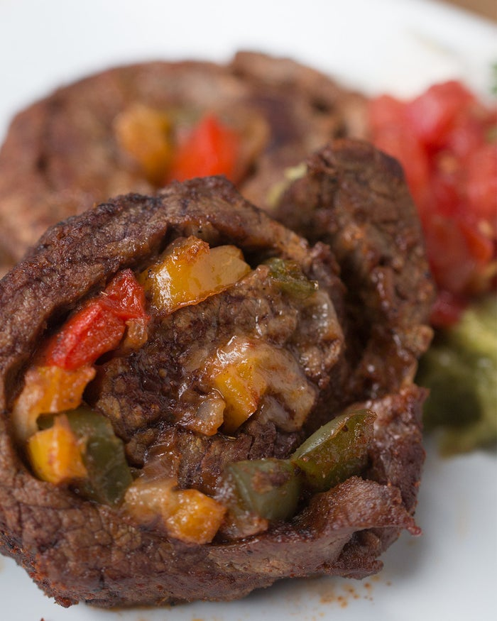 Fajita Steak RollsServings: 3-4 INGREDIENTS1 onion, sliced1 tablespoon garlic½ cup green bell pepper½ cup red bell pepper½ cup yellow bell pepperSalt, to tasteSeasoning½ teaspoon chili powder½ teaspoon paprika⅛ teaspoon cayenne½ teaspoon cumin½ teaspoon garlic powder½ teaspoon dried oregano½ teaspoon salt½ teaspoon pepper1½ pound flank steak, thinly sliced½ cup monterey jack cheeseLonger wooden toothpicks or cut wooden skewersPREPARATION1. Preheat oven to 350˚F/180˚C.2. In a bit of oil, saute onion, garlic and bell peppers, until soft.3. Combine chili powder, paprika, cayenne, cumin, garlic powder, salt, and pepper in a dish and use to season the flank steak on both sides.4. Lay the steak flat on a cutting board with the grain running up and down.5. Place sauteed onions & peppers in the middle of the steak, leaving an inch or so on both ends.6. Cover the onions & peppers with a layer or monterey jack cheese.7. Tightly roll up the meat from left to right, this will ensure that you will be cutting against the grain when you cut the meat.8. Stick toothpicks through the sides of the roll to help them hold their shape and use a sharp knife to cut in between the toothpicks.9. In an oven safe skillet, cook over high heat until a nice crust has developed and flip. Repeat with the other side10. Bake for 10 minutes, or until cooked to your preference.11. Enjoy!