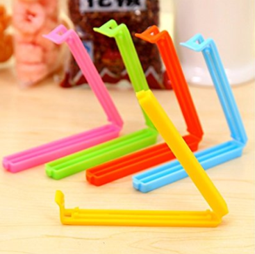 Five reusable seal clips of different colours on a table