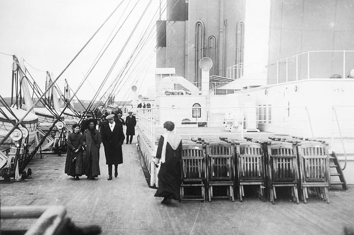 Passengers stroll past neatly arranged deck chairs on the deck of the ship.