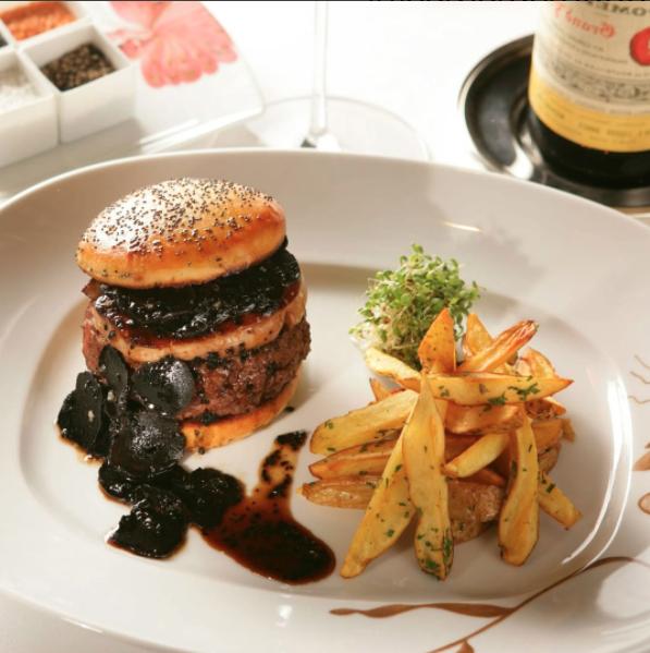 Esta exquisita hamburguesa viene acompañada con una botella de vino para ayudarte a asimilar tu costosa decisión.