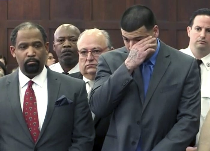 Aaron Hernandez (right) wipes his eyes in court Friday.