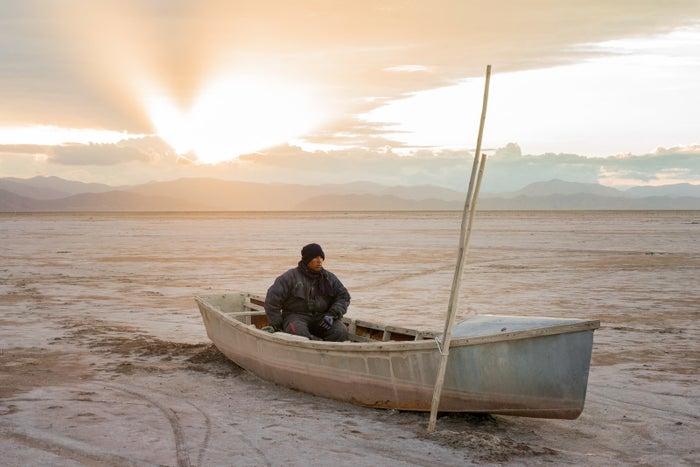 Félix Sequeiros sentado em um barco no atualmente seco Lago Poopó, na Bolívia.