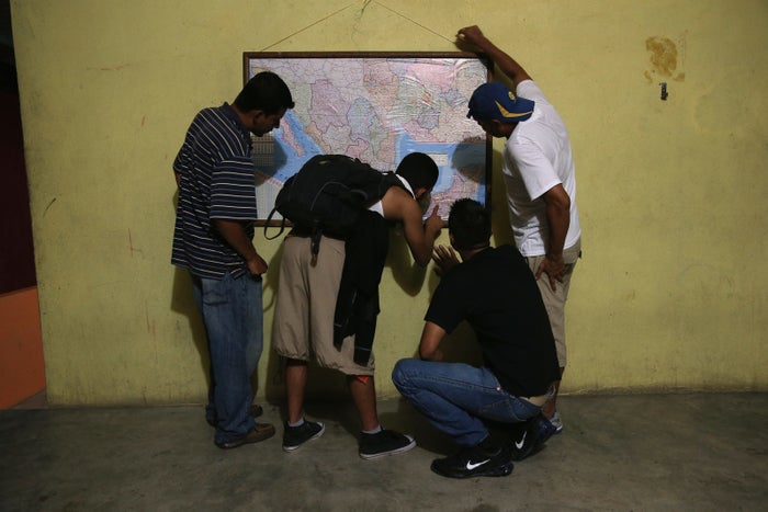 Honduran immigrants inspect map of Mexico while staying at a shelter for undocumented immigrants.