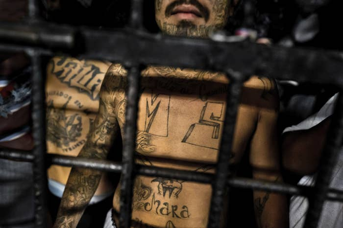 A member of the Mara Salvatrucha gang stands behind bars in a cell at a detention center in San Salvador.