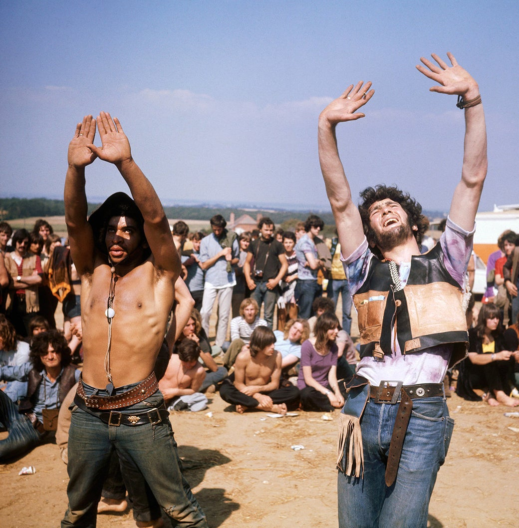 A group of hippies watch on as several others dance during the Isle of Wight Festival in 1969.