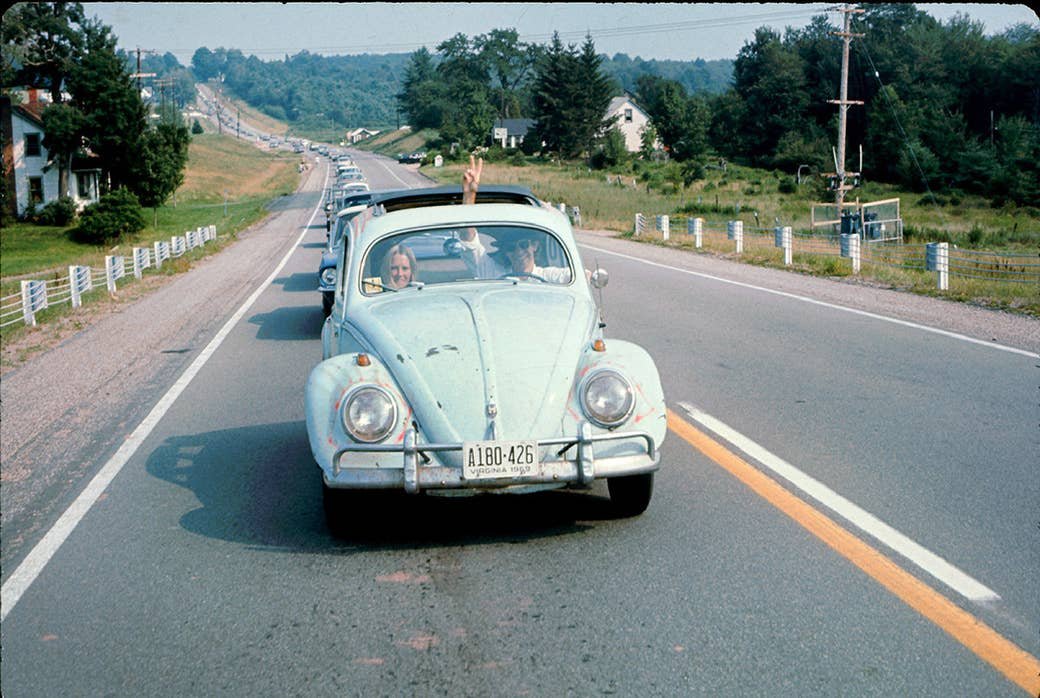 A man driving a Volkswagen Beetle makes his way to the Woodstock Music and Arts Fair as he flashes a peace sign through the sunroof in 1969.