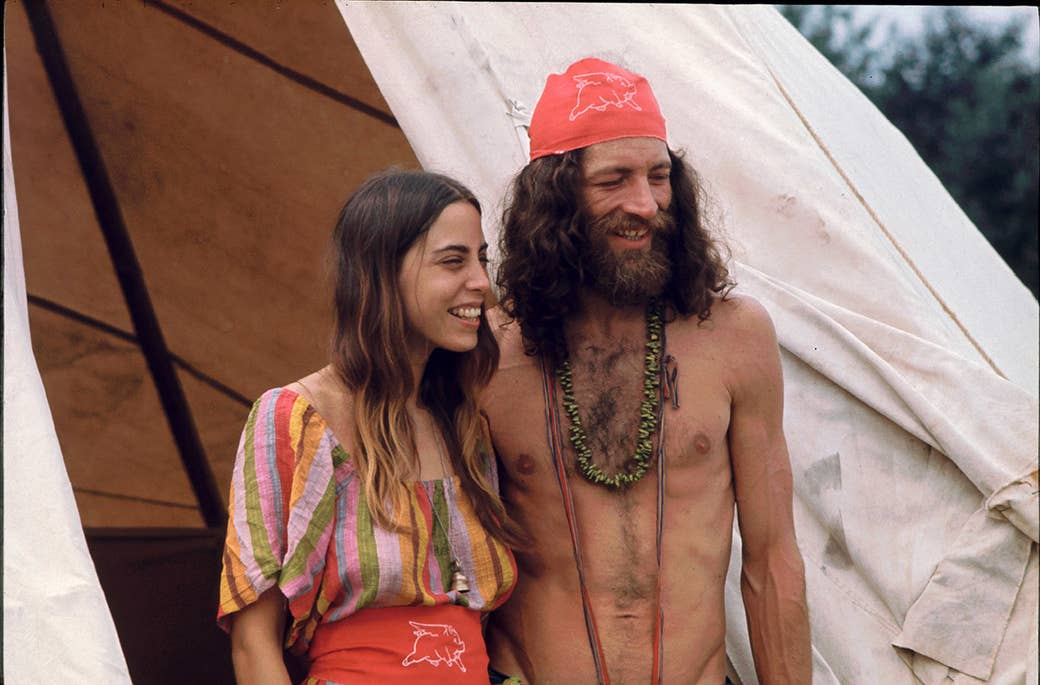 A couple attending the Woodstock Music and Arts Fair smile while standing outside the shelter they built.