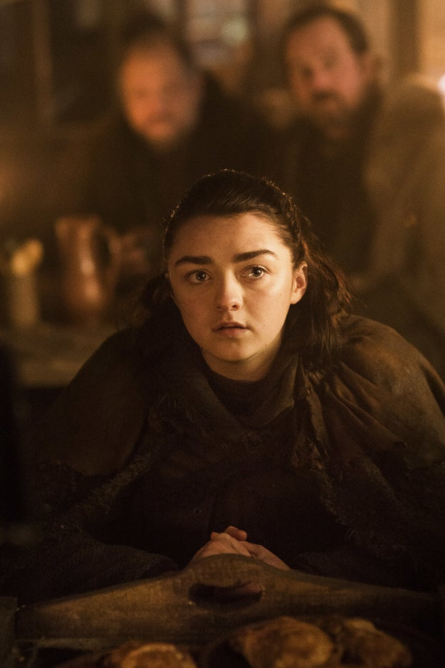 Arya sitting down in what seems to be some sort of pub.