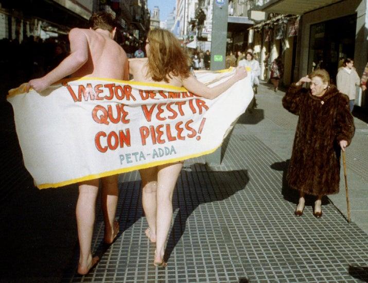 Una mujer con un abrigo de piel observa a dos activistas de PETA que se manifiestaron en Madrid el 20 de enero de 1994.