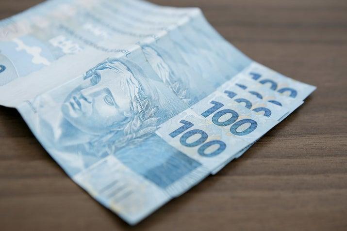 Бразильский реал поставляется в различных цветах, включая синий R $ 100 банкноту выше, на которых изображены подводные растения, морские звезды, кораллы, и глава Република, национальный символ Федеративной Республики Бразилии.