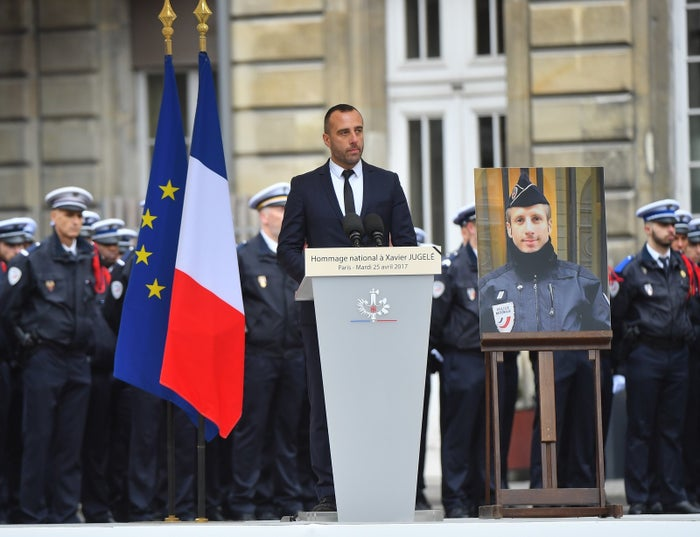 Etienne Cardiles speaks Tuesday in Paris next to a photo of his slain husband.