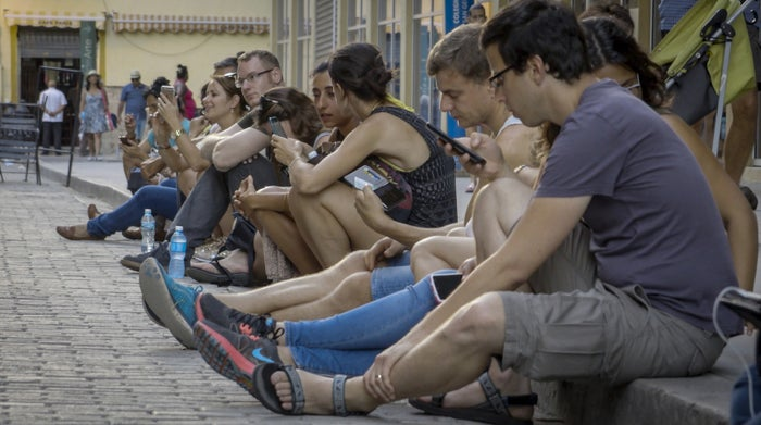 People use public WiFi to connect their devices in a street of Havana.