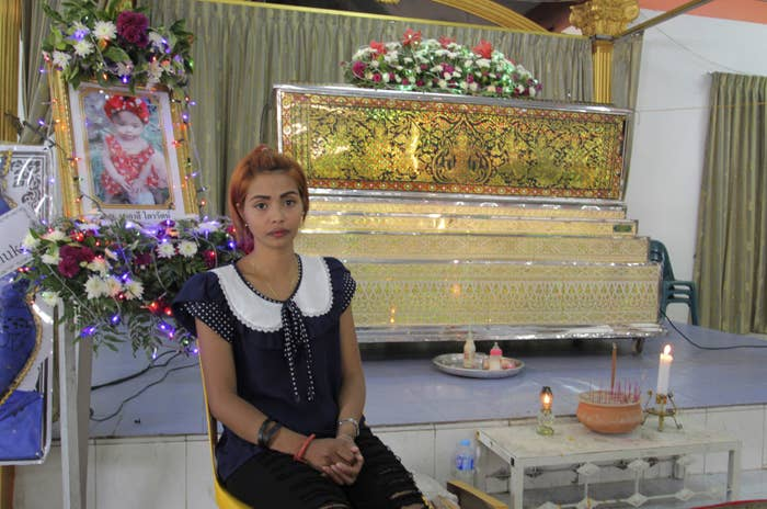 Chiranut Trairat, mother of the 11-month-old baby girl, sits in front of her daughter's coffin.