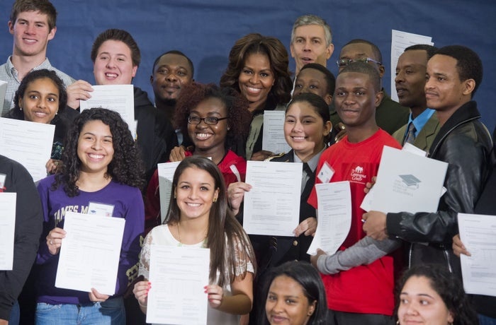 Michelle Obama stands with students as they hold up the FAFSA during a workshop in 2014.