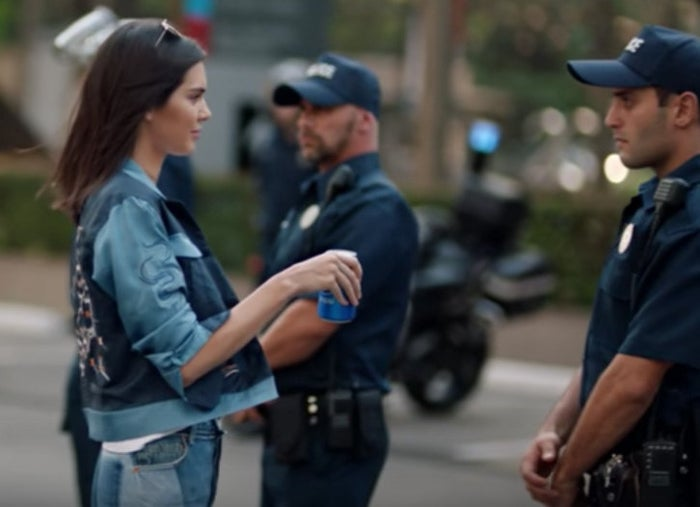 """The police officer takes a sip, looks at his fellow cop, and smiles – as if to say, """"Hey, maybe we should protest too?""""And this is only the shortened version of the ad. There's a ~2.5-minute special as well that features a woman in a hijab looking at photos and a man playing the cello."""