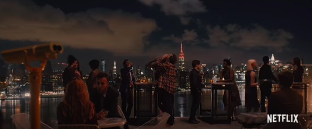 In the trailer, we see Dev having fun and living his life in New York City...