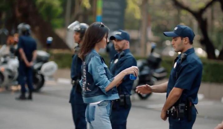 Los poderes mágicos de la Pepsi hacen que el policía se una a la causa y todos gritan en celebración.