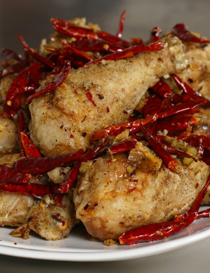 Servings: 6-8INGREDIENTS8 drumsticksOil for fryingSalt, to taste Pepper, to tasteBatter:1 cup cornstarch½ cup all-purpose flour1 teaspoon salt¼ teaspoon black pepper1 cup waterSpice Mix:1½ tablespoon Szechuan pepper powder1 tablespoon red pepper flakes1 tablespoon cumin3 tablespoon sugar1 teaspoon saltAromatics:6 cloves garlic chopped2 tablespoons ginger chopped1 cup dried chillies3 tablespoons vegetable oilPREPARATIONPat dry drumsticks and season with salt and pepper. Air-dry in refrigerator for at least 2 hours and up to overnight.Prepare all aromatics for stir frying, and combine spice mix ingredients in a small bowl. Stir together until evenly mixed.Heat ¾ inch of vegetable oil to 300°F/150˚C in cast-iron skillet or large pot. Whisk together ingredients for batter until smooth. Dip individual drumsticks in the batter to coat, allowing excess batter to drip before placing in frying oil.Fry drumsticks 8-10 minutes, turning halfway through. Remove and rest chicken on paper towels to drain for at least 10 minutes. Turn oil temperature up to 375°F/190˚C. Re-fry drumsticks for 3-4 minutes or until golden brown, turning frequently. Remove to paper towels to drain.In a wok or large sauté pan, heat 3 tablespoons of vegetable oil over high heat. Once it smokes, carefully add aromatics and stir fry for 90 seconds. Add chicken and sprinkle half of the spice mix evenly over the top. Toss chicken and aromatics to coat evenly, then add the other half of the spice mix and repeat. Remove from heat.Arrange chicken on plate and top with stir fried aromatics.Enjoy!