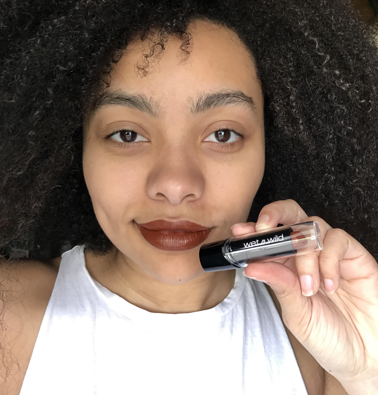 A person holding a tube of the wet n wild lipstick by their mouth