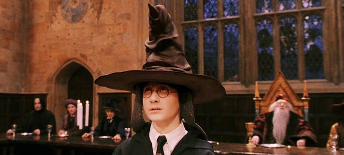 A young boy with glasses looks up at a large leather witch hat on his head. He wears a tie and robe