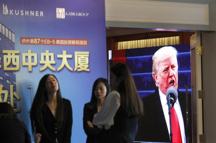 A screen shows footage of Donald Trump as workers wait for investors during an event promoting EB-5 investment in a Kushner Companies development.