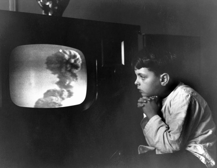 Raymond Carlin, age 7, of the Bronx is held spellbound before his television screen as he watches a live atomic detonation in 1955.