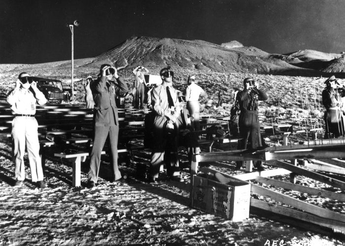 """Observers wearing protective eyewear witness the detonation of nuclear artillery shell, codenamed """"Grable,"""" at the Nevada Proving Grounds on May 25, 1953. The long shadows are the result of the nuclear fireball. The shot was the 10th in a series of 11 nuclear detonations conducted in Operation Upshot–Knothole and marked the first time a nuclear device had been fired from a cannon."""