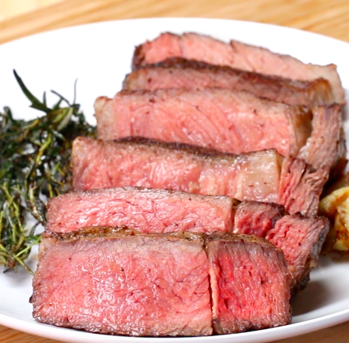Servings: 2INGREDIENTS1 1½-pound rib eye steak, 1-inch thick 2 tablespoons kosher salt2 tablespoons black pepper4 tablespoons canola oil3 tablespoons butter2 sprigs thyme2 bunches rosemary2 cloves garlic, peeled and crushedPREPARATION1. Preheat oven to 250°F/120˚C.2. Season the steak evenly with the salt and pepper on all sides.3. Place the steak on a wire rack on top of a baking sheet. Bake for 35 minutes. 4. Heat the canola oil in a skillet or stainless steel pan over high heat until smoking. Sear the steak on one side for 30 seconds, then flip. Immediately add the butter, thyme, rosemary, and garlic, swirling the pan to melt the butter quickly. 5. Place the herbs and garlic on top of the steak, and push the steak towards the top of the pan. Tilt the pan towards you to pool the butter near the bottom. Using a spoon, continuously scoop the butter over the top of the steak for about 30-45 seconds. This helps not only flavor the steak, but also helps cook the steak faster. If you prefer your steak medium or medium-well, cook your steak longer. 6. To test the doneness of your steak, lightly press the tip of your left index finger to the tip of your left thumb. The fleshy area below the thumb should feel like what rare steak feels like when pressing the surface of the steak. For medium-rare steak, touch your middle finger to your thumb and press the area below your thumb. For medium, touch your fourth finger to your thumb. For well-done, touch your pinky to your thumb.7. Rest the steak for 10 minutes on a cutting board. Slice, then serve!